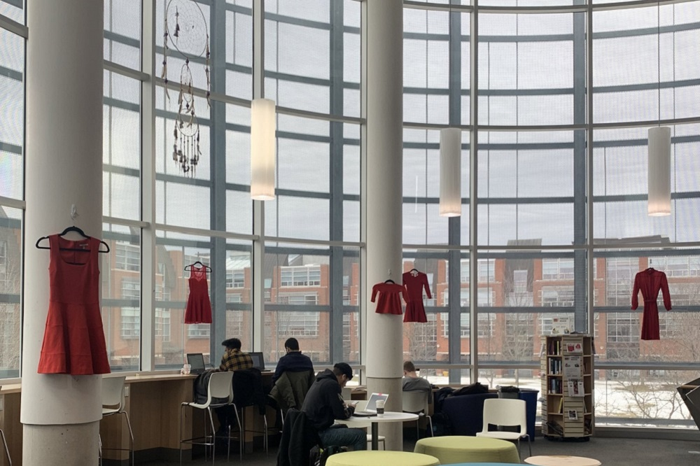 Red dresses displayed in Ontario Tech University's North Oshawa Campus Library.