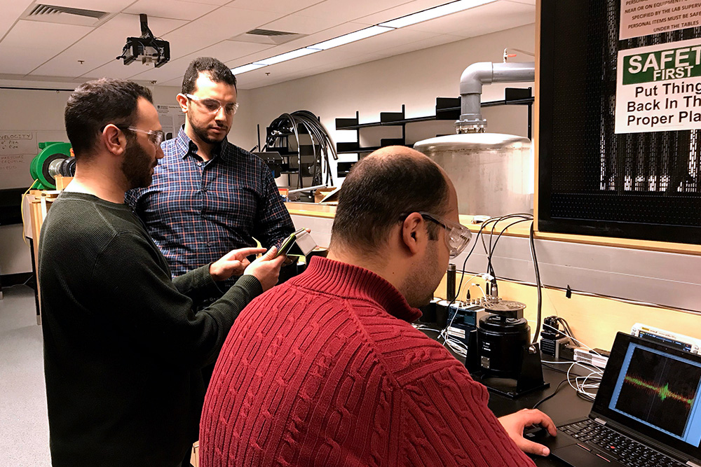 From left: Mohammed Alziadeh (Ontario Tech PhD candidate) discusses seismic test results with Mahmoud Shaaban, PhD (Ontario Tech doctoral fellow) while Omar Sadek (Ontario Tech PhD candidate, seated) takes a sample measurement.