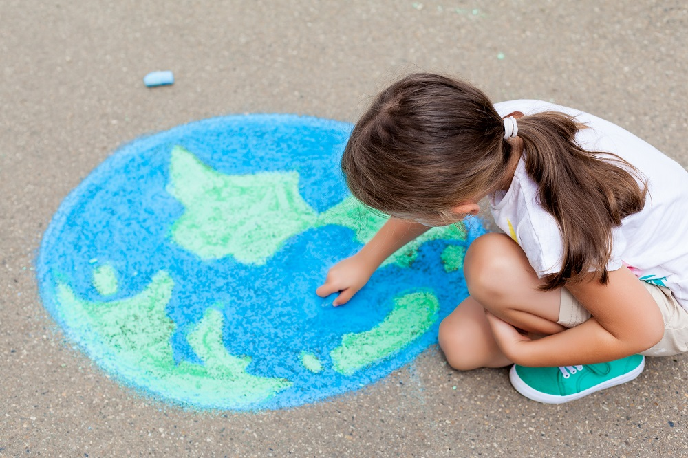 Child drawing globe on the ground with chalk