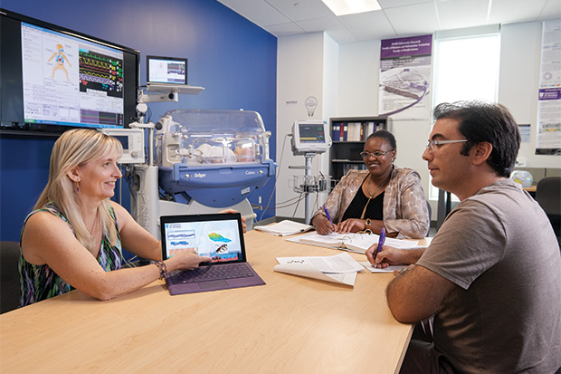 Dr. Carolyn McGregor (left) consults with members of her research team in 2018 in the Health Informatics Research Laboratory at Ontario Tech University (with Catherine Inibhunu [centre] and Roozbeh Jalali).