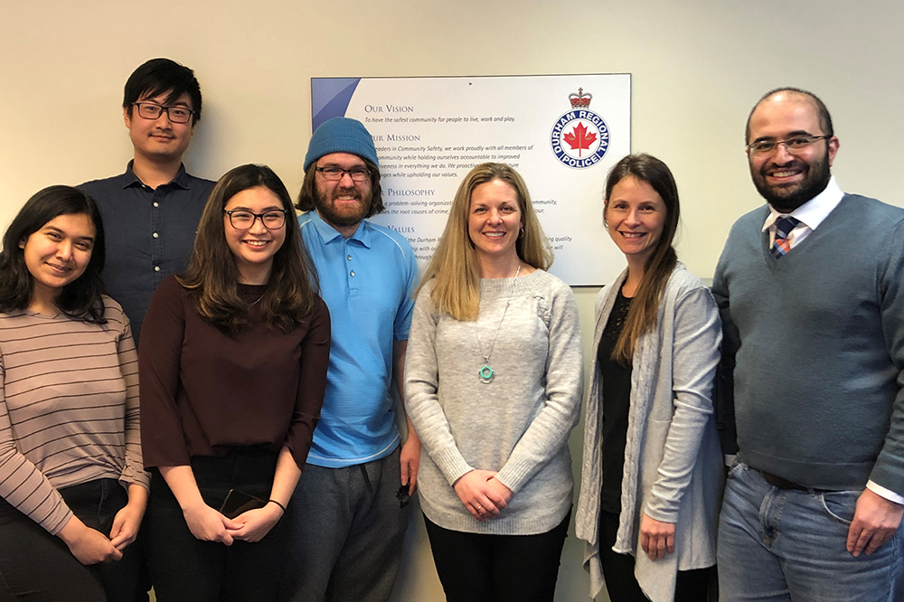 (Please note: image from February 2020, prior to physical distancing and mask protocols), From left: Ontario Tech University Faculty of Business and Information Technology (FBIT) students Atiya Nova, Wen Bo Yu, Angela Tabafunda and Chris Bull; Holly Britton, Health, Wellness and Safety Manager. Durham Regional Police Service (DRPS); Dr. Krystle Martin, Ontario Shores Research Scientist and DRPS Consultant; and Dr. Pejman Mirza-Babaei, Associate Professor, FBIT, Ontario Tech University.