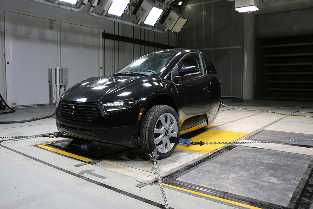 Dynamic testing of the three-wheel Electra Meccanica Solo EV in the ACE Climatic Wind Tunnel at Ontario Tech University. The one-person electric vehicle has two front wheels and one rear wheel.