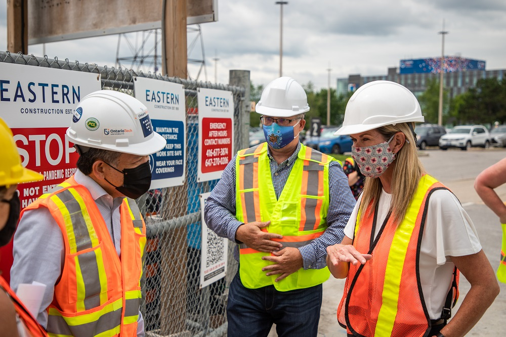 From left: Larry Brual, Senior Project Manager with Ontario Tech's Office of Campus Infrastructure and Sustainability, with the university's President and Vice-Chancellor Dr. Steven Murphy and the Honourable Jill Dunlop, Ontario's Minister of Colleges and Universities, at the construction site of Ontario Tech's newest building, Shawenjigewining Hall